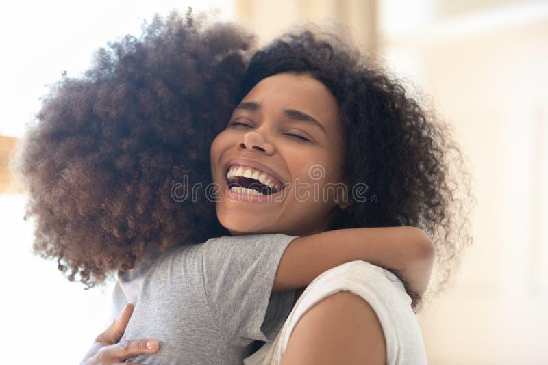 Madre soltera africana extática feliz que abraza a la hija linda del niño fotografía de archivo