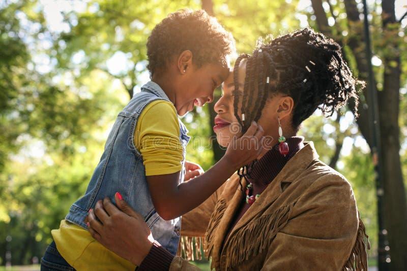 Madre soltera afroamericana en parque con su hija imagenes de archivo