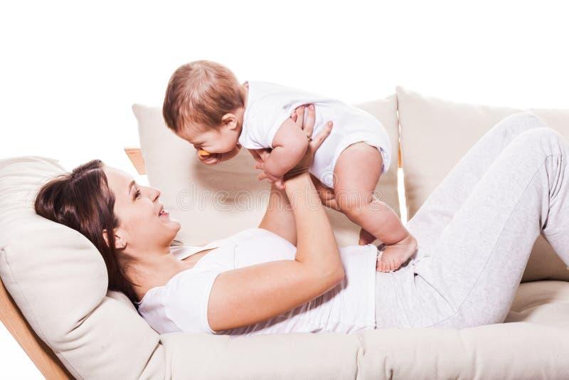 Madre sonriente feliz con el bebé imagenes de archivo