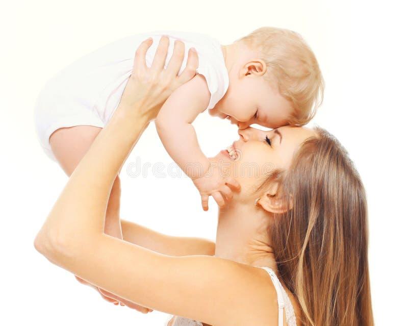 Madre sonriente feliz del primer que juega con su bebé aislado en blanco imagenes de archivo