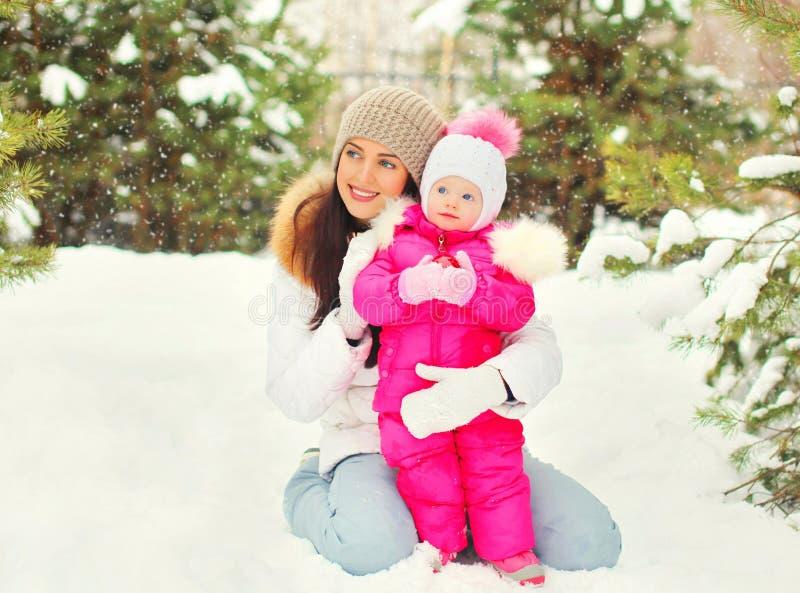 Madre sonriente feliz del retrato del invierno con el niño sobre los copos de nieve nevosos del árbol de navidad imagen de archivo