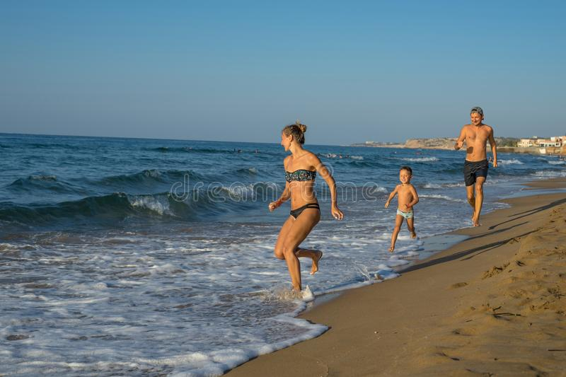 Madre sonriente feliz, padre y su jugar y funcionamiento del hijo en la playa Concepto de familia amistosa Días de verano felices foto de archivo