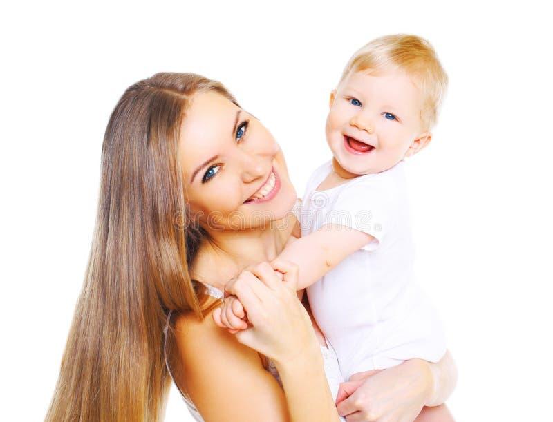 Madre sonriente feliz que juega con el bebé en un fondo blanco fotografía de archivo