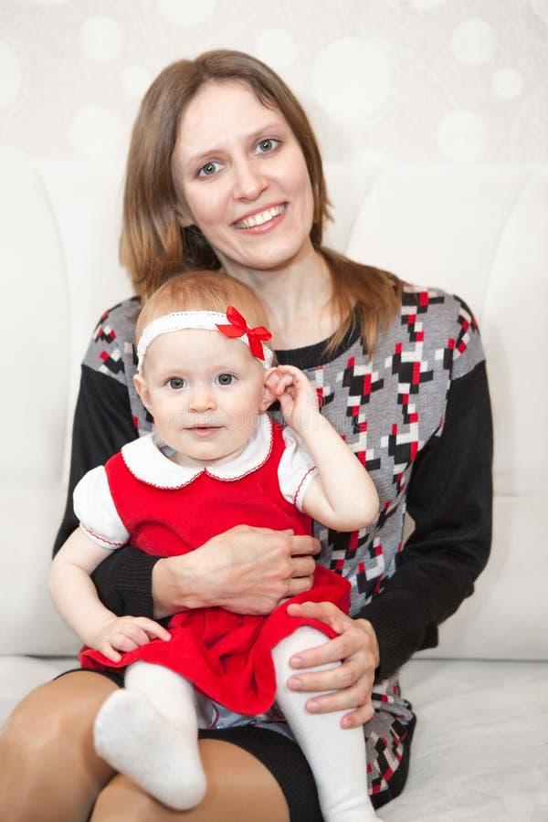 Madre sonriente feliz que se sienta con el bebé en rodillas fotos de archivo