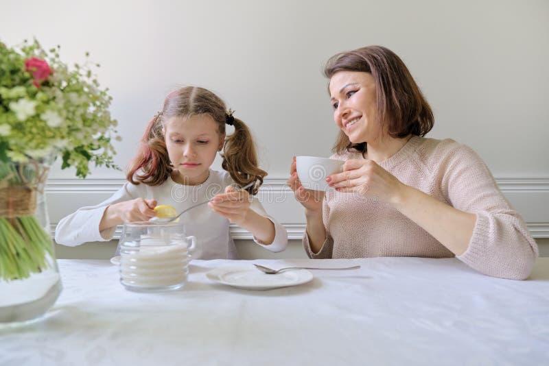 Madre sonriente feliz y pequeña hija que beben en la tabla de tazas imagenes de archivo