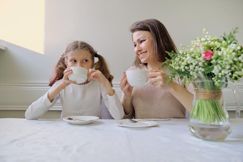 Madre sonriente feliz y pequeña hija que beben en la tabla de tazas imagen de archivo libre de regalías