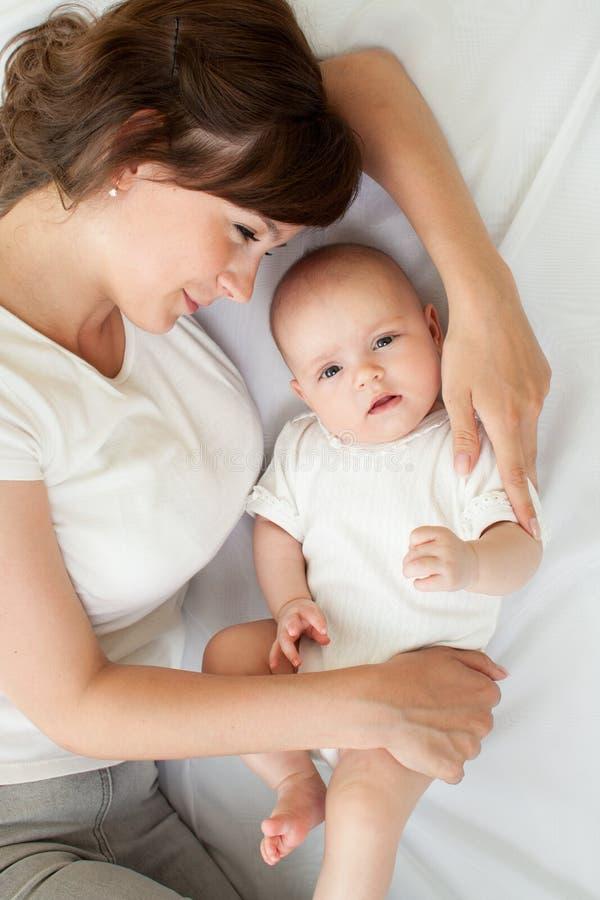Madre sonriente feliz y su bebé que mienten en cama en casa, visión superior fotos de archivo libres de regalías