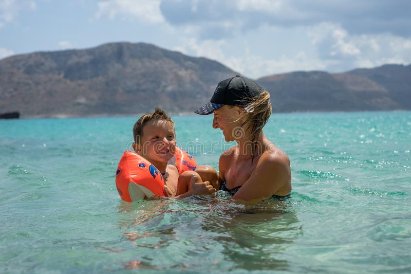 Madre sonriente feliz y su hijo que juegan y que corren en la playa Concepto de familia amistosa Días de verano felices foto de archivo