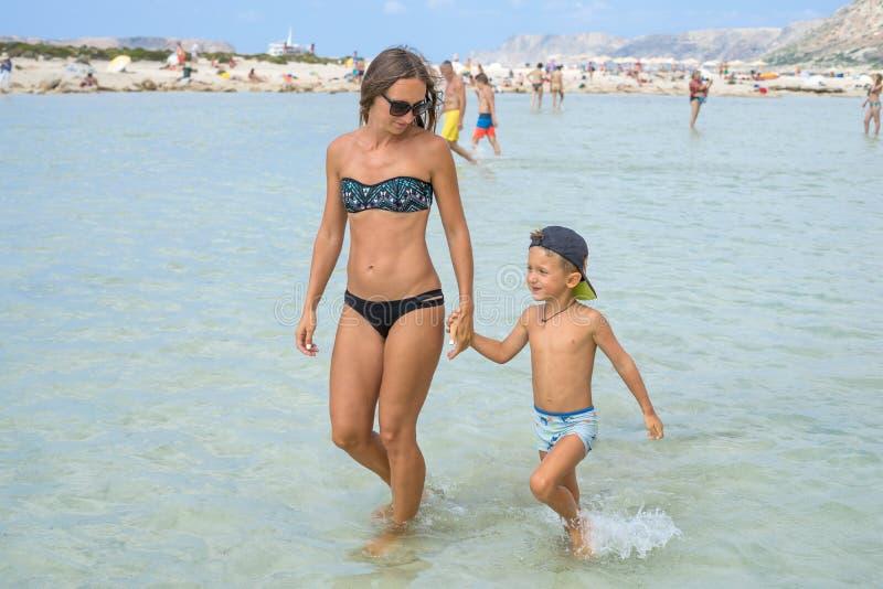 Madre sonriente feliz y su hijo que juegan y que corren en la playa Concepto de familia amistosa Días de verano felices Laguna de fotos de archivo