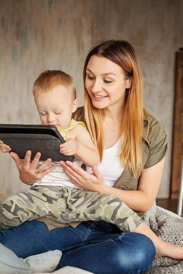 Madre sonriente joven con el hijo que usa la tableta digital imágenes de archivo libres de regalías