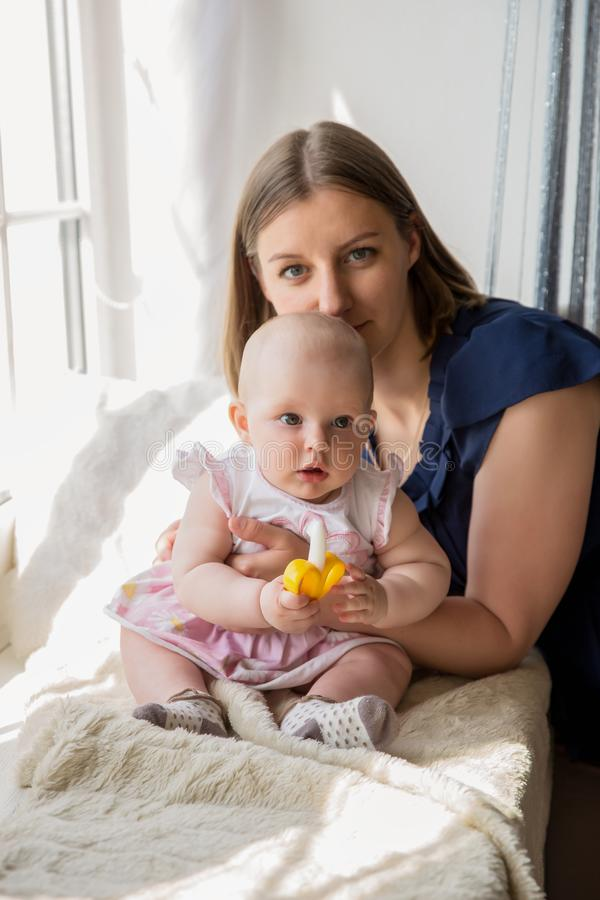 Madre sonriente que abraza a su hija del bebé en la ventana fotos de archivo
