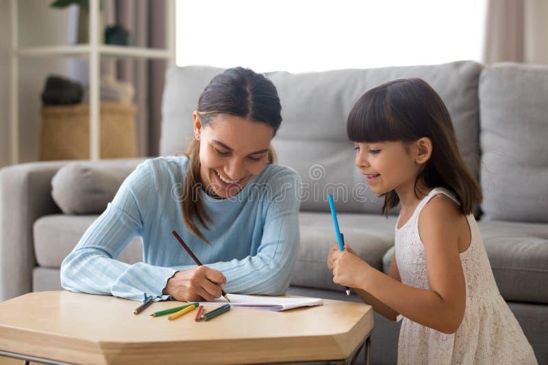 Madre sonriente que ayuda a la muchacha preescolar que enseña al niño lindo a dibujar foto de archivo libre de regalías
