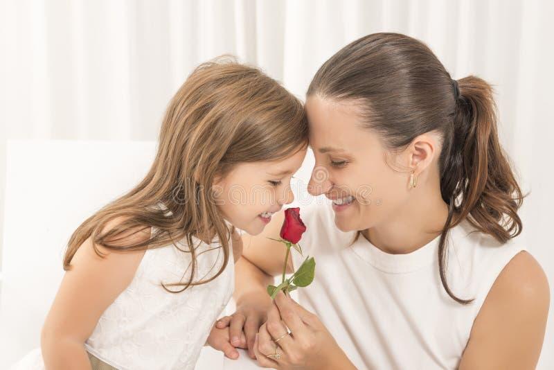 Madre sonriente que consigue las flores de su hija el día de madre fotos de archivo libres de regalías