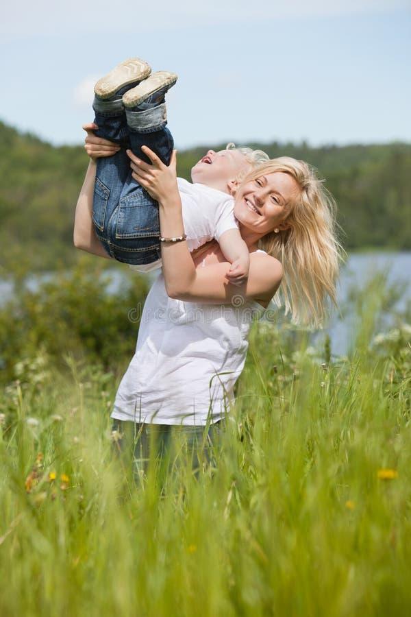 Madre sonriente que juega con el niño imagen de archivo libre de regalías
