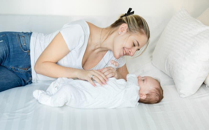 Madre sonriente que juega en cama con su bebé lindo fotografía de archivo libre de regalías