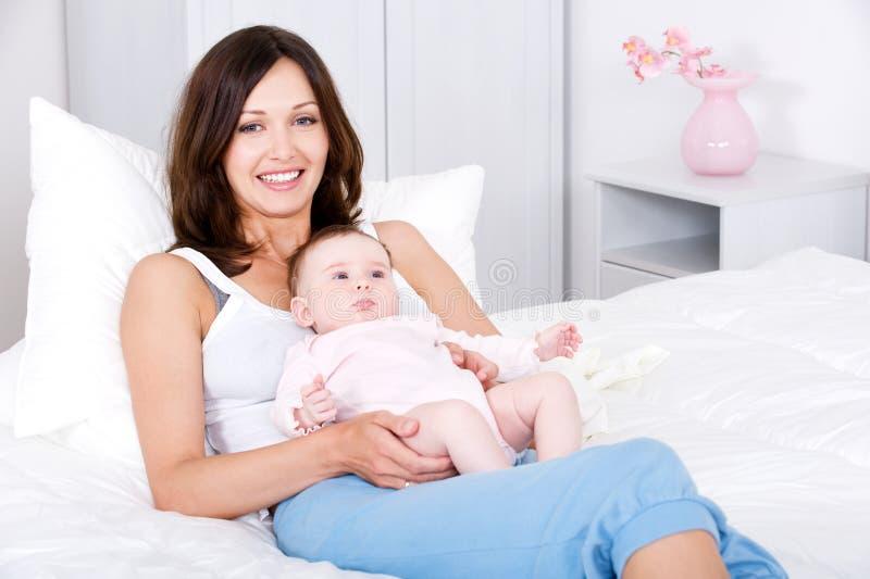 Madre sonriente que se sienta con el bebé en el país foto de archivo
