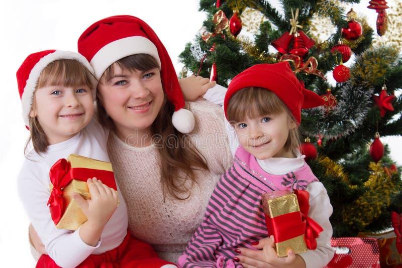 Madre sonriente y dos hijas debajo del árbol de navidad imagen de archivo libre de regalías