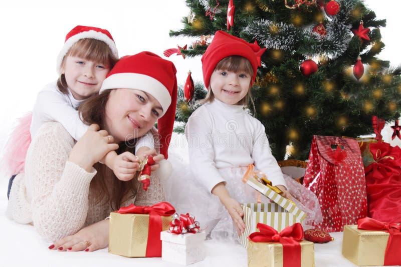 Madre sonriente y dos hijas debajo del árbol de navidad imagen de archivo