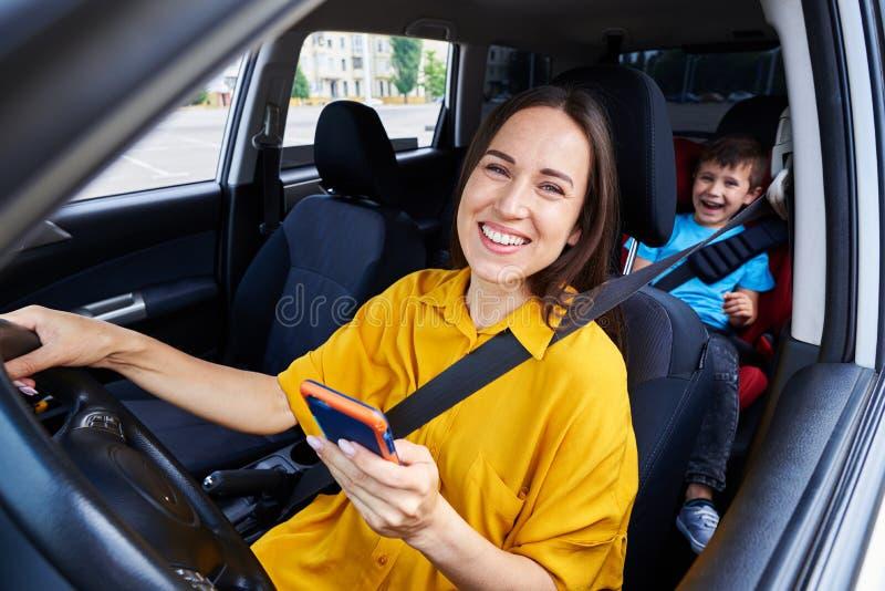 Madre sorridente che conduce un'automobile, tenente telefono immagini stock libere da diritti