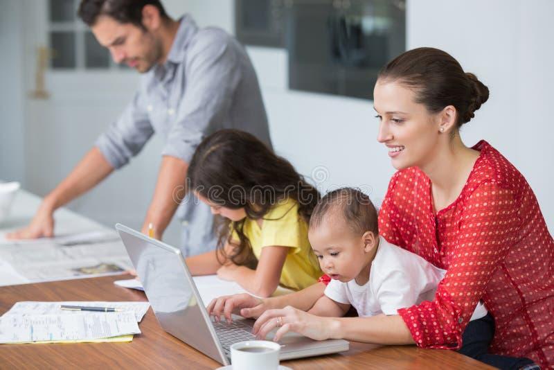Madre sorridente che lavora al computer portatile con il bambino mentre studio della figlia immagini stock libere da diritti