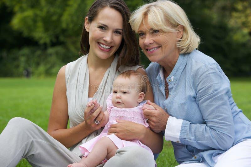 Madre sorridente con il bambino e la nonna all'aperto fotografia stock