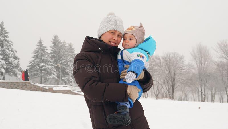 Madre sorridente con il suo poco bambino sul pendio della neve nell'inverno immagini stock