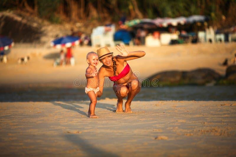 Madre sorridente con un bambino sulla spiaggia immagine stock