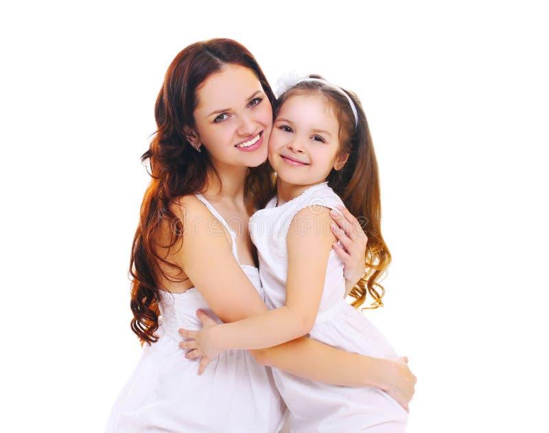 Madre sorridente felice che abbraccia la figlia del piccolo bambino su bianco immagine stock libera da diritti
