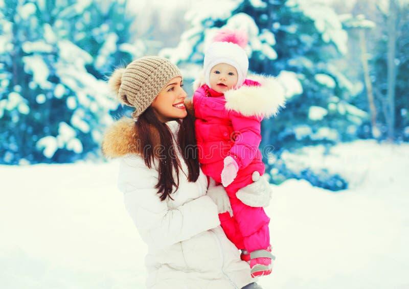 Madre sorridente felice del ritratto di inverno con il bambino sulle sue mani sopra l'albero di Natale nevoso immagine stock libera da diritti