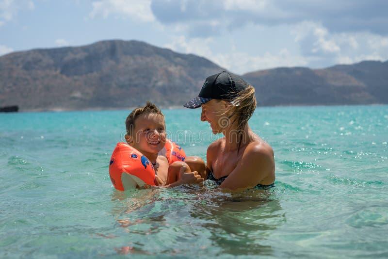 Madre sorridente felice e suo il figlio che giocano e che corrono sulla spiaggia Concetto della famiglia amichevole Giorni di est fotografia stock