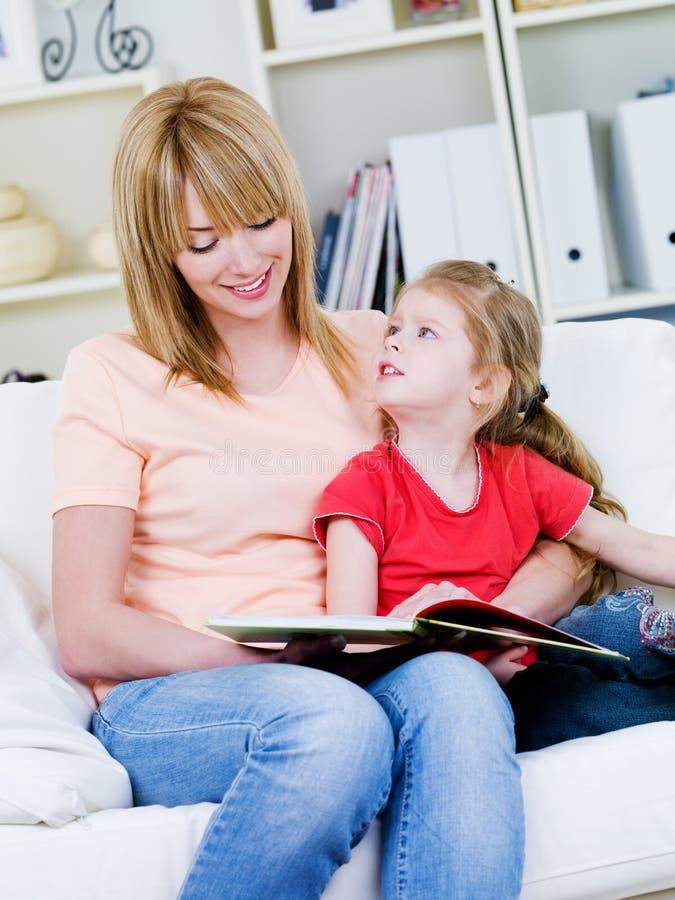 Madre studing su hija para leer foto de archivo libre de regalías