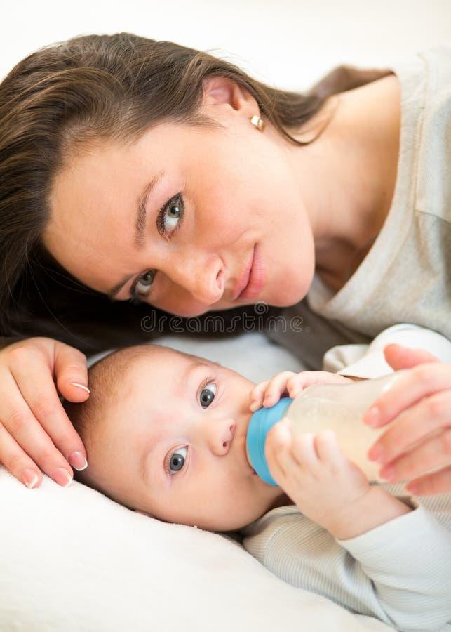 Madre sveglia a casa che alimenta il figlio del bambino con un latte fotografia stock
