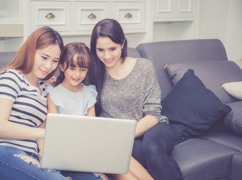Madre, tía y niño teniendo tiempo junto lerning con usar el ordenador portátil en casa foto de archivo libre de regalías
