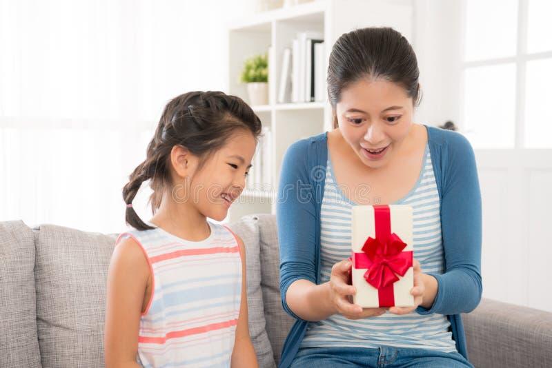Madre tocada feliz de abrir el regalo de la hija foto de archivo libre de regalías