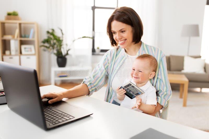 Madre trabajadora con el bebé y el ordenador portátil en casa imagen de archivo libre de regalías