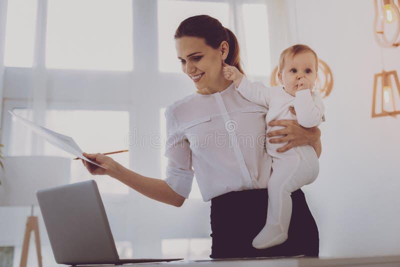 Madre trabajadora joven que sonríe mientras que cuida a su pequeño bebé rubio-cabelludo fotos de archivo