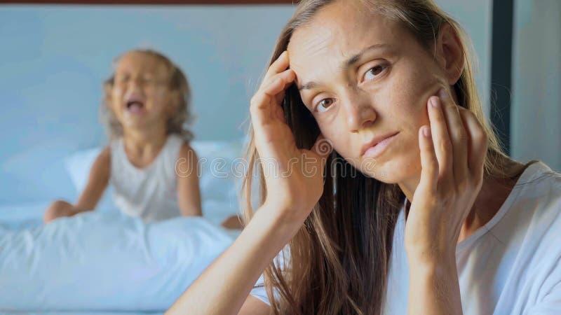 Madre trastornada con la almohada de griterío enojada del pequeño niño en el fondo imágenes de archivo libres de regalías