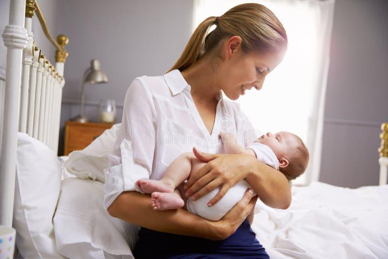Madre vestita per il bambino della tenuta del lavoro in camera da letto immagini stock libere da diritti