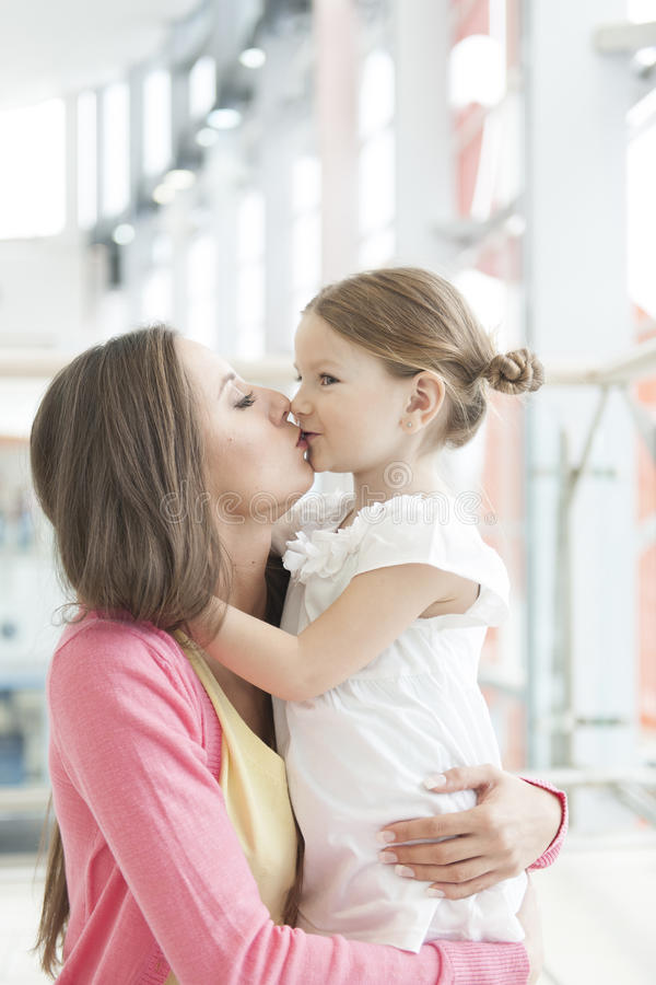 Madre y abrazo y beso de la hija fotos de archivo libres de regalías