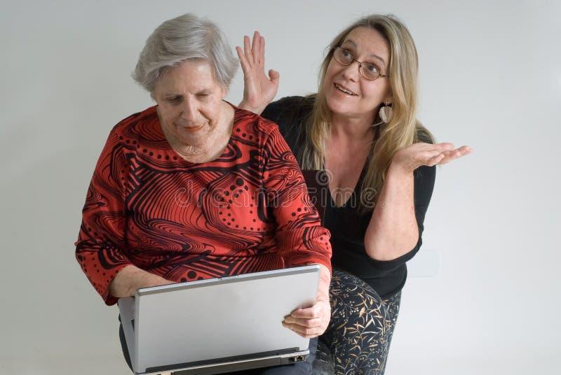 Madre y abuela que trabajan en una computadora portátil fotografía de archivo libre de regalías