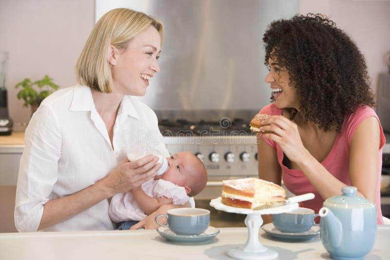 Madre y bebé con el amigo que come la torta imágenes de archivo libres de regalías