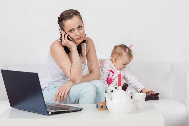 Madre y bebé con el teléfono. imagenes de archivo