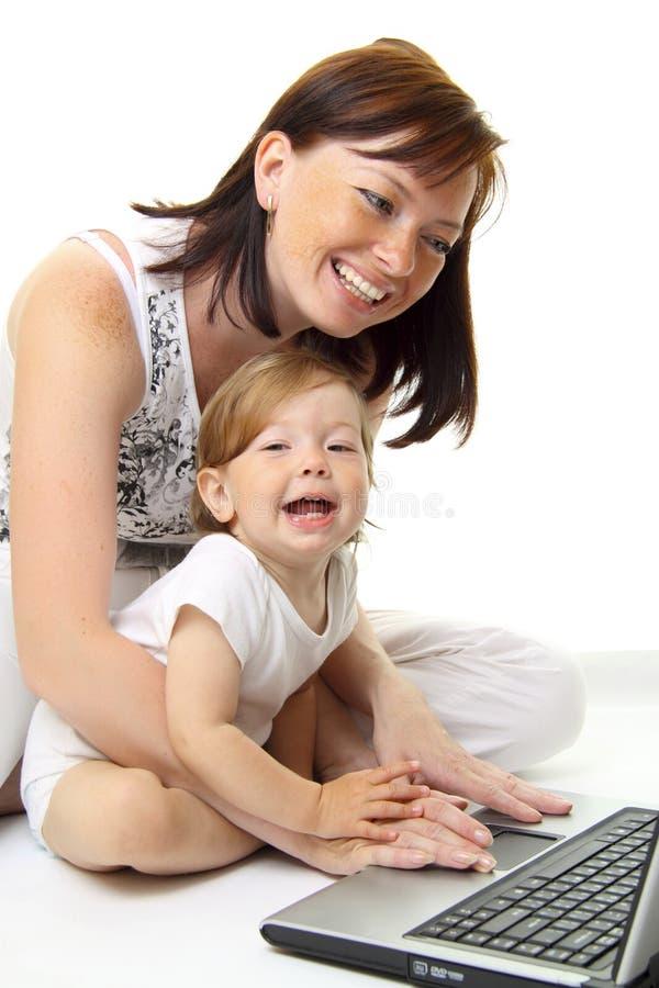 Madre y bebé con la computadora portátil imágenes de archivo libres de regalías
