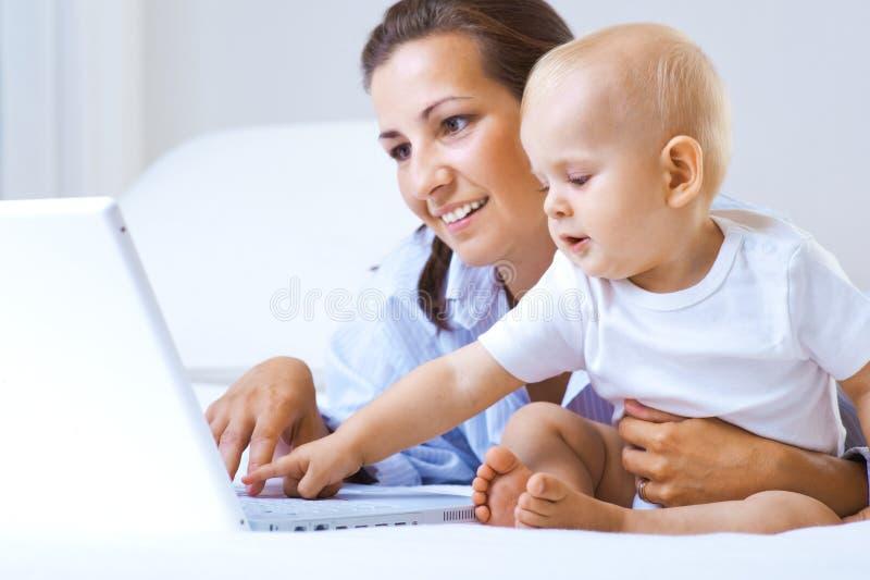 Madre y bebé con la computadora portátil imagenes de archivo