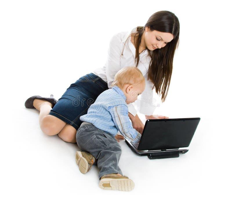 Madre y bebé con la computadora portátil fotografía de archivo libre de regalías