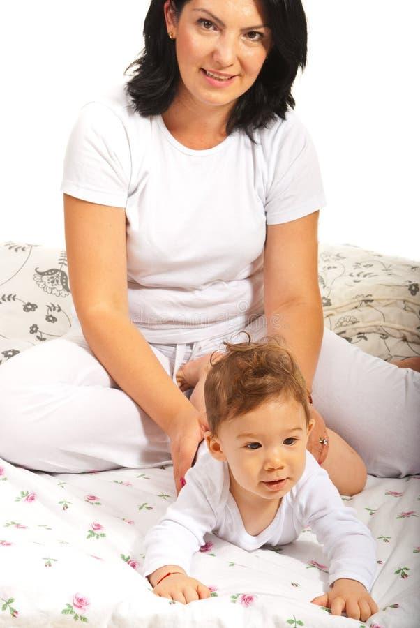 Madre y bebé en cama foto de archivo