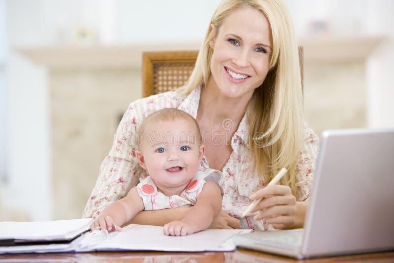 Madre y bebé en comedor con la computadora portátil imagen de archivo libre de regalías