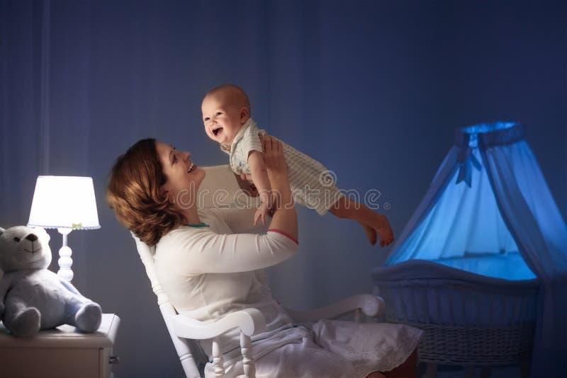 Madre y bebé en dormitorio oscuro fotos de archivo libres de regalías