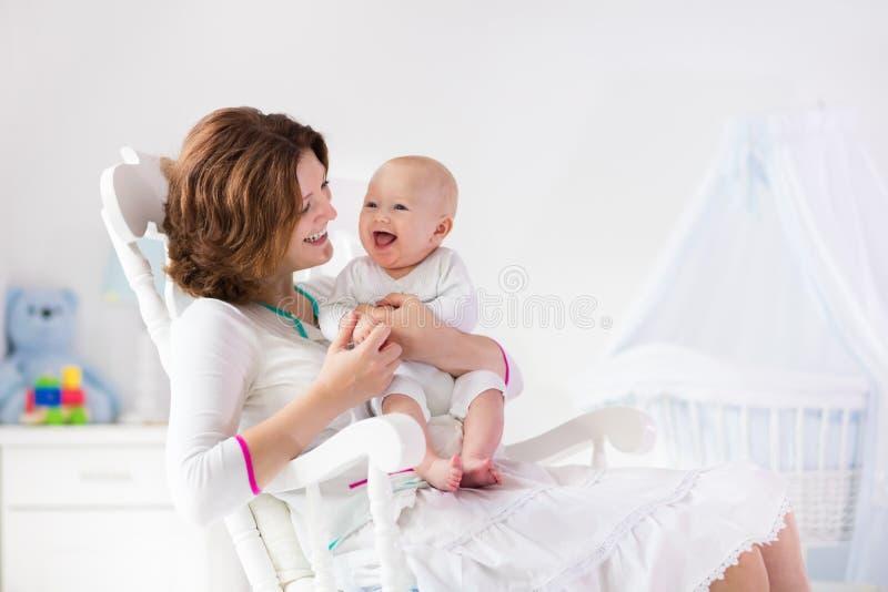 Madre y bebé en el dormitorio blanco fotos de archivo