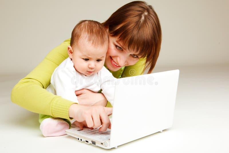 Madre y bebé en la computadora portátil imagenes de archivo